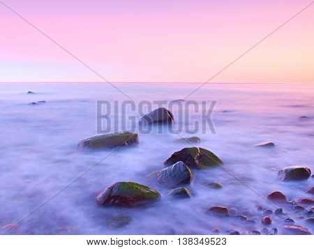Sunset At Rocky Coast Of Sea. Low Shutter Speed For Smooth Water Level And Dreamy Effect