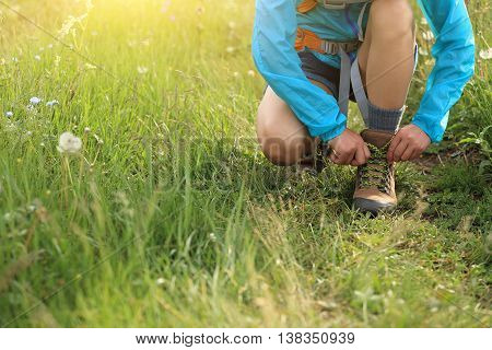 oung woman hiker tying shoelace on trail in grassland