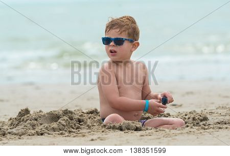tough and handsome boy child with sunglasses, sitting on the beach. the kid is digging in the sand looking around