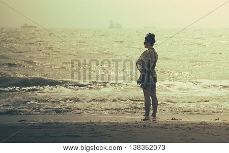 wonderful woman standing in front of the sea on the beach at sunset. she's wearing a dress and she's looking and thinking at the sea