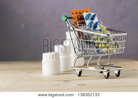 Shopping cart with different tablets and various pill bottle on wooden table