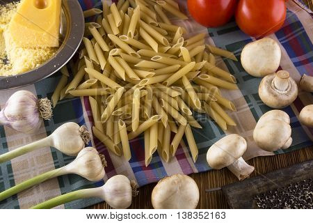 Pasta, tomatoes, garlic champignon and grated cheese on wooden background.