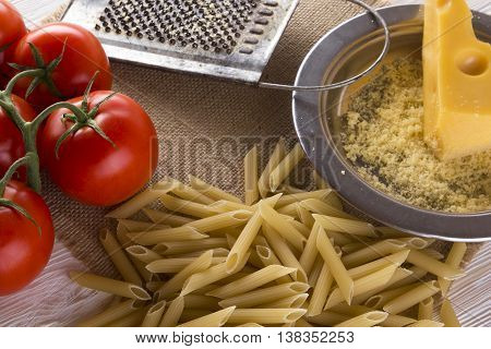 Pasta, tomatoes and grated cheese on wooden background.