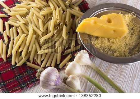Pasta, grated cheese and garlic on wooden background