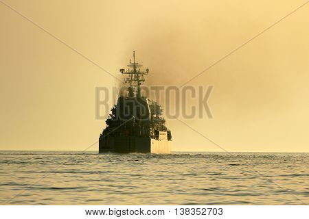 silhouette of a warship at sea on a sunset background