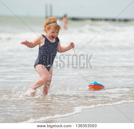 she's wearing an adorable flower swimsuit and she's running with a toy boat through the sea