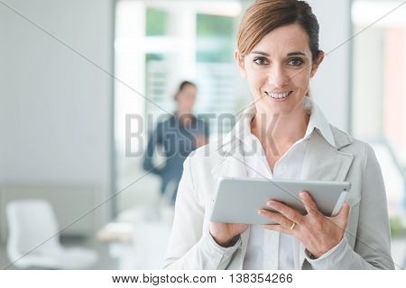 Confident smiling business woman standing in the office and using a digital touch screen tablet