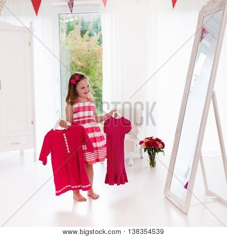 Little girl choosing dresses in white bedroom. Child watching mirror reflection holding pink dress choosing outfit. Girls nursery. Shopping clothing for kids. Dressing room interior for children.