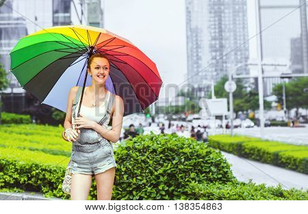 Young attractive woman standing with a multi-colored umbrella on a background of the urban landscape. Woman smiling in a positive mood.