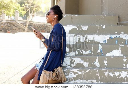 Cheerful Black Lady Sitting Outdoors On Steps With Mobile Phone