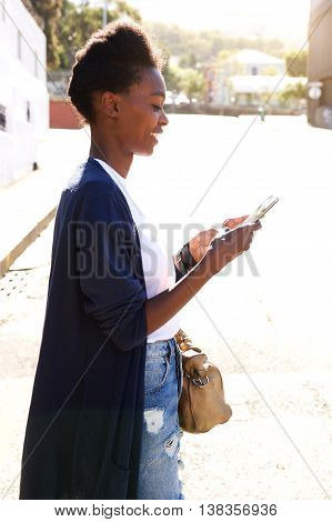 Happy Young Woman Using Mobile Phone Outdoors