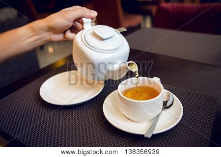 man pours tea from a white teapot in a tea Cup, saucer and teaspoon, a sugar bowl are on the table