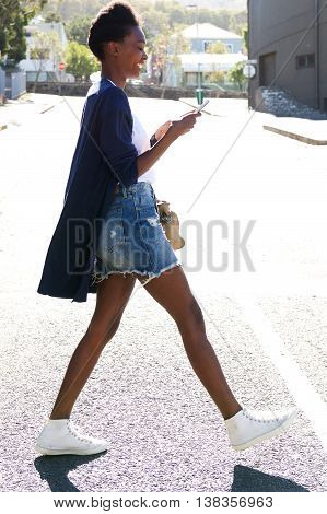 Smiling African Woman Walking With Cell Phone