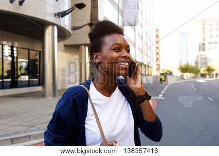 Smiling Black Woman Walking Outdoors And Talking On Cellphone