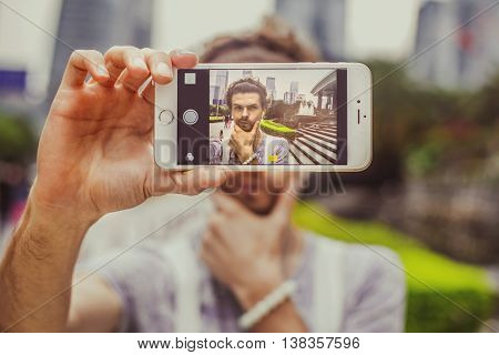 Young attractive man doing selfie phone on the background of skyscrapers. Portrait of a man with intricate facial expressions.Guy holding chin with one hand.