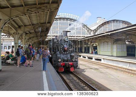 SAINT - PETERSBURG, RUSSIA - JULY 10, 2016: Vitebsky Railway Station. People take pictures near coal retro-locomotive on the platform.