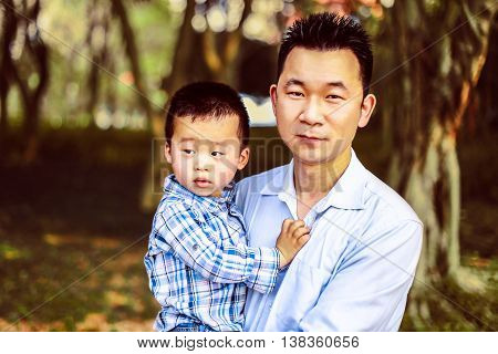 Chinese dad holding his little son in the park. Boy looking to the side.