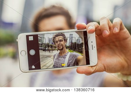 Handsome guy photographed himself on the phone on the background of skyscrapers and smiles. Best selfie.