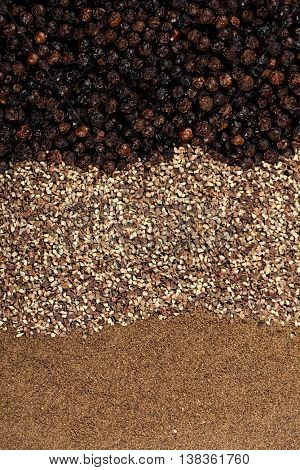 whole, crashed and ground black peppercorns background