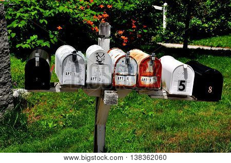 Fitzwilliam New Hampshire - July 11 2013: A row of rural USPS mail boxes stands on a lawn opposite the village green *