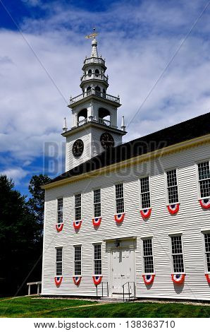Jaffrey Center New Hampshire: Red white and blue patriotic bunting hangs from the windows of the austere 1775 Original Meeting House church with its elegant steeple and bell tower