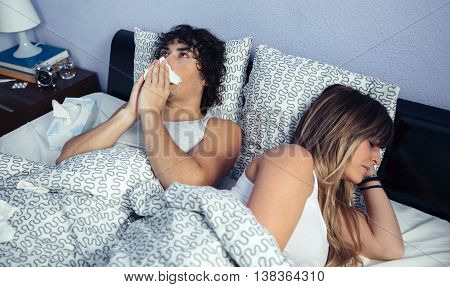 Sick man sneezing and covering nose with tissue lying on bed side to young woman sleeping. Sickness and healthcare concept.