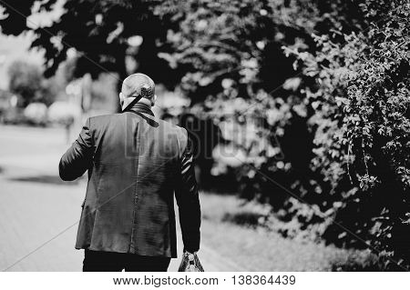 Man On Jacket With Cane Skull Head On Shoulders And Bag On Hand. Black And White