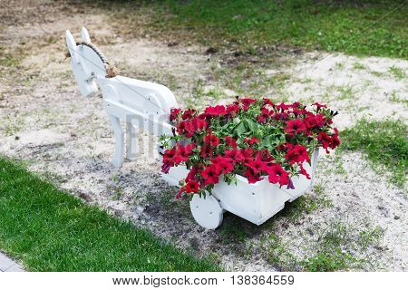 Flowerbed cart with bright pink flowers. White wood decorative wagon with small pony horse and petunias. Modern garden decoration.