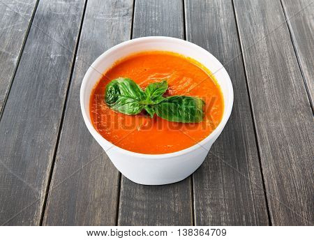 Spanish cuisine hot food delivery - tomato diet cream soup gazpacho at gray rustic wood background in white plastic plate