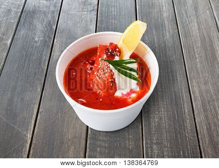 Russian cuisine food delivery - borscht soupcloseup in white plastic plate at gray wooden table background. Hot dish on wood