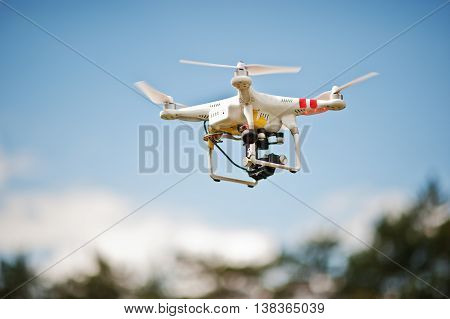 Drone Quad Copter With High Resolution Digital Camera Flying In The Blue Sky
