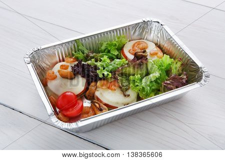 Healthy food and diet concept. Take away of fitness meal. Weight loss nutrition in foil boxes. Vegetables, lettuce and mozarella cheese with cherry tomatoes and shrimps closeup at white wood