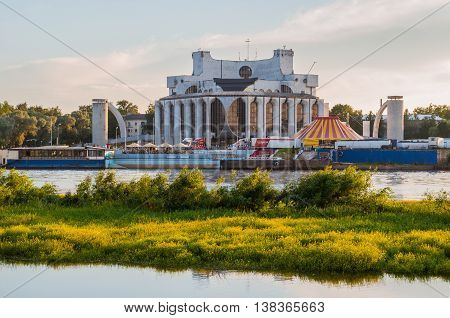 VELIKY NOVGOROD RUSSIA - JUNE 21 2016. Summer sunset architecture view of Novgorod Regional Drama Theatre at the bank of the Volkhov river in summer evening. Picturesque architecture landscape