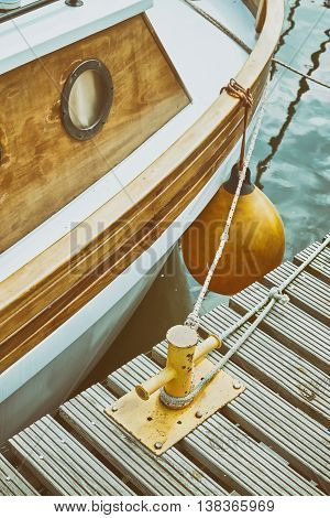 Wooden Yacht Moored To Bollard In Marina.