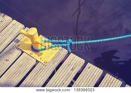 Yellow Mooring Bollard With Blue Rope.