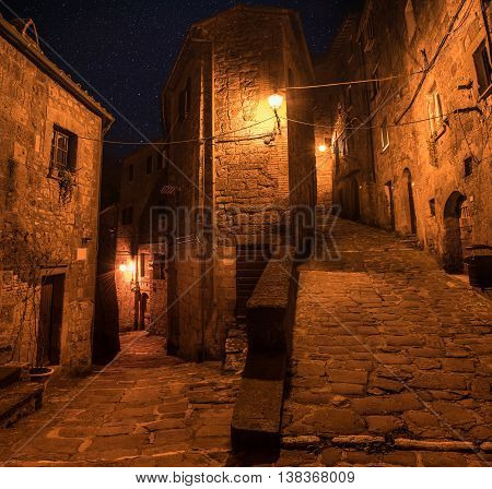Street of ancient medieval tuff city Sorano at night  - travel european background