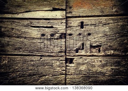 Closeup of an old  wooden antique door with lot of keyholes, grunge rustic background