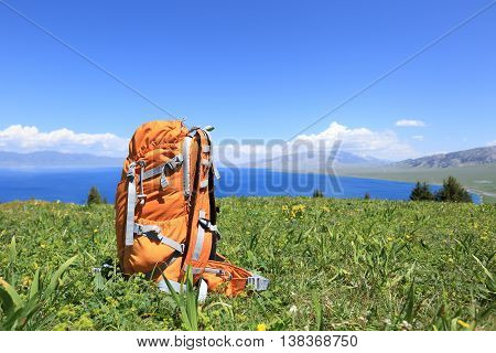 one hiking backpacker on mountain peak grassland