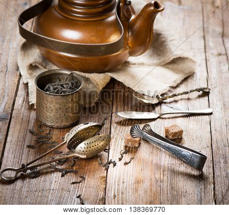 Dry black tea brown clay kettle tea strainer sugar on a old wooden background.
