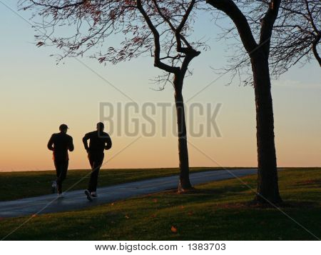 Two Runners Silhouetted Against Sky