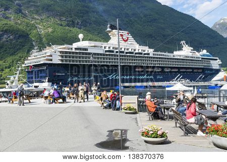 GERANGER, NORWAY - JUNE 29: Geirangerfjord seaport full of tourists and big cruise ferry in the background on June 29, 2016 in Geiranger, Norway.