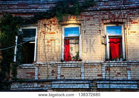 three open windows on a brick building in the evening
