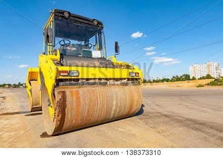 Road roller stands on asphalt surface during the new road construction process.