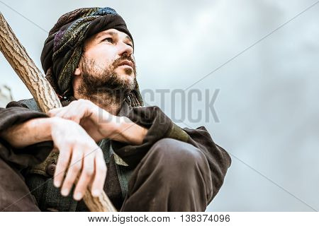 Man in the patterned turban with a stick sitting and seriously looking to the side on a light background. Selective focus on face toned.