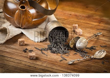Conceptual still life with black tea on a old wooden background. Selective focus is on the dry tea.
