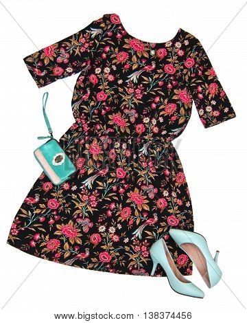Fashion still life Women's clothing: black dress in a floral pattern blue shoes clutch bag pendant Top view