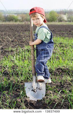 Kleine jongen te graven op veld met grote schop