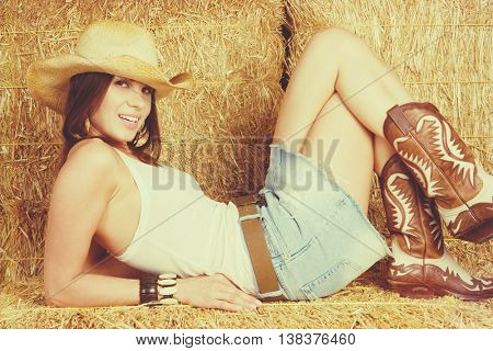 Pretty smiling cowgirl laying in hay