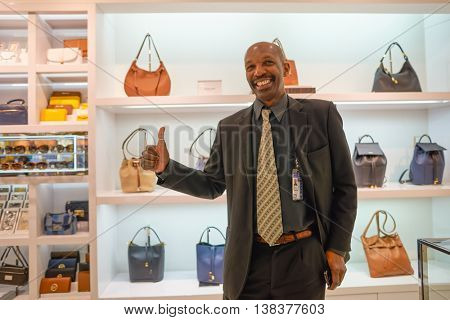 NEW YORK - APRIL 06, 2016: indoor portrait of seller in Michael Kors store at JFK Airport. Michael Kors Holdings is an American luxury fashion company established in 1981 by designer Michael Kors.
