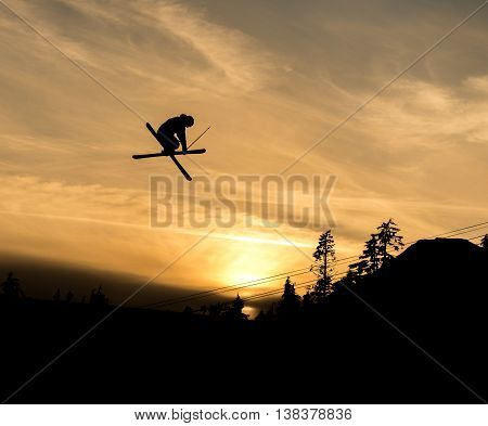 silhouette of skier doing grab off a jump in the sunset